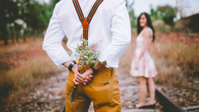 man holding flowers looking at woman
