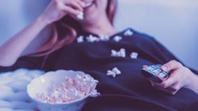 woman watching movie eating popcorn
